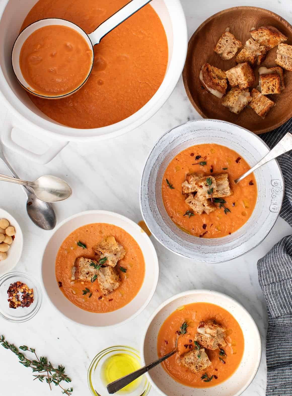 Creamy Vegan Tomato Soup with Grilled Cheese Croutons in bowls