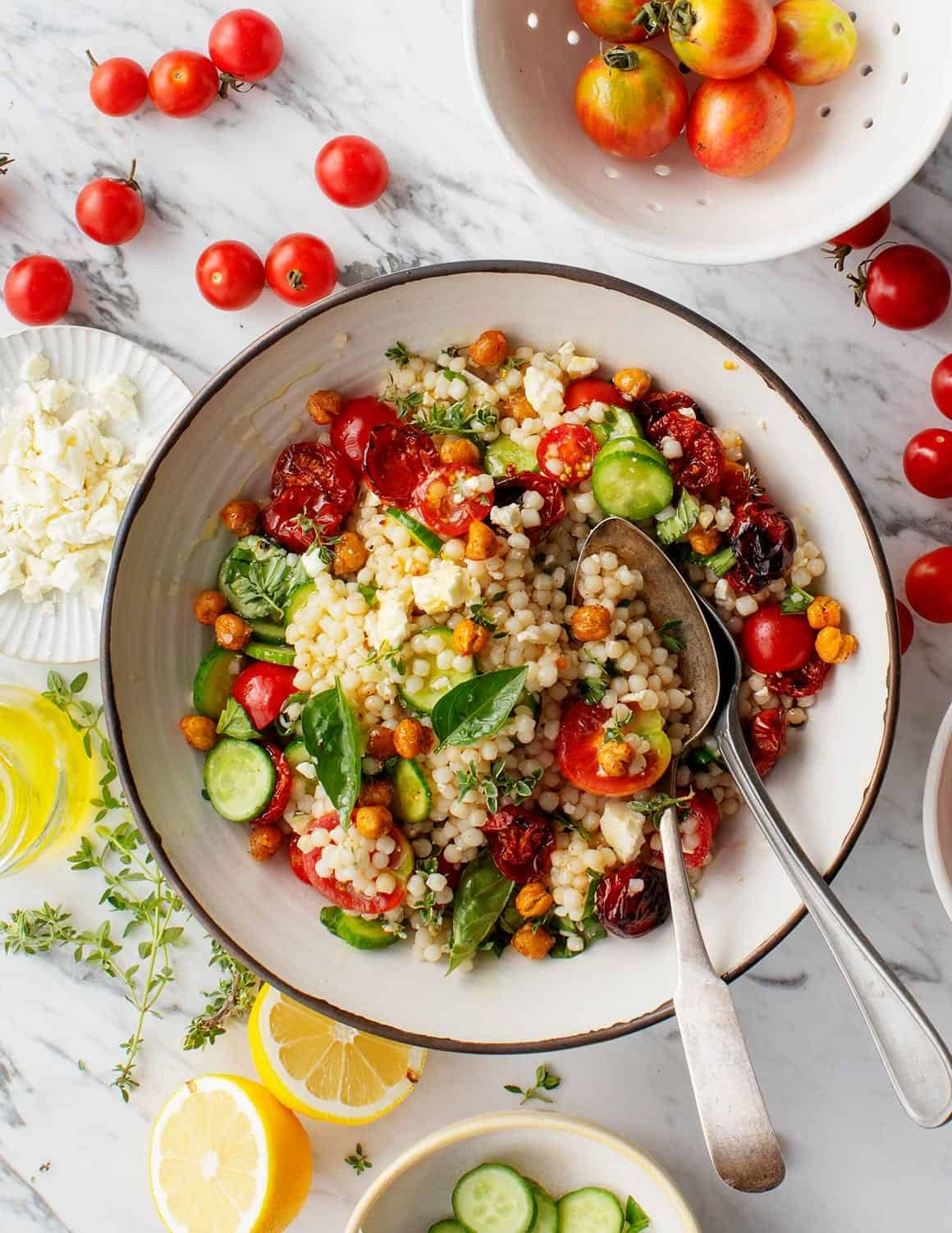 Roasted Cherry Tomato & Thyme Couscous Salad in a bowl with spoons