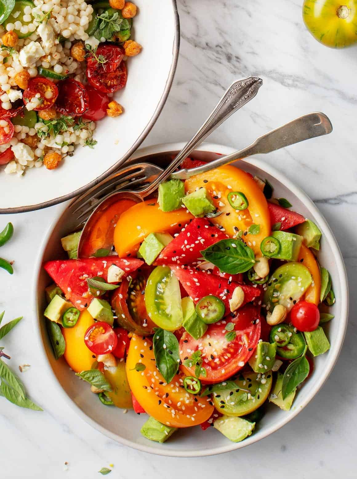 Spicy Tomato Watermelon Salad in a bowl with serving utensils