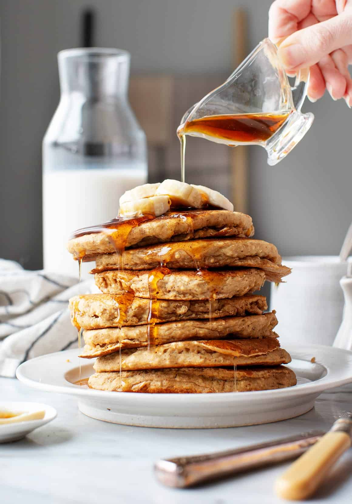 Vegan banana pancakes on a plate with maple syrup