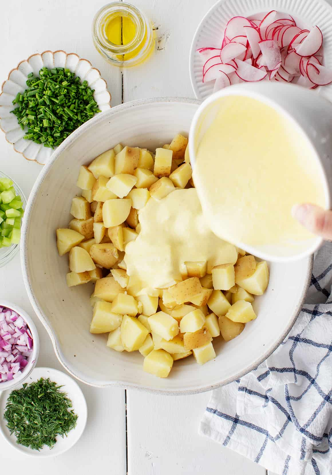 Pouring dressing over cooked potatoes in a mixing bowl