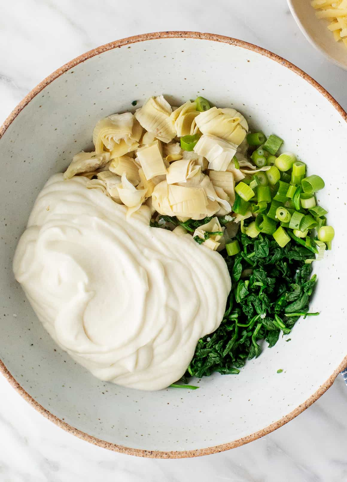 Creamy sauce, artichokes, scallions, and spinach in a bowl