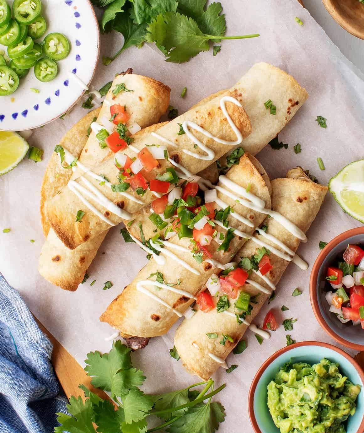Taquitos with sour cream and pico de gallo