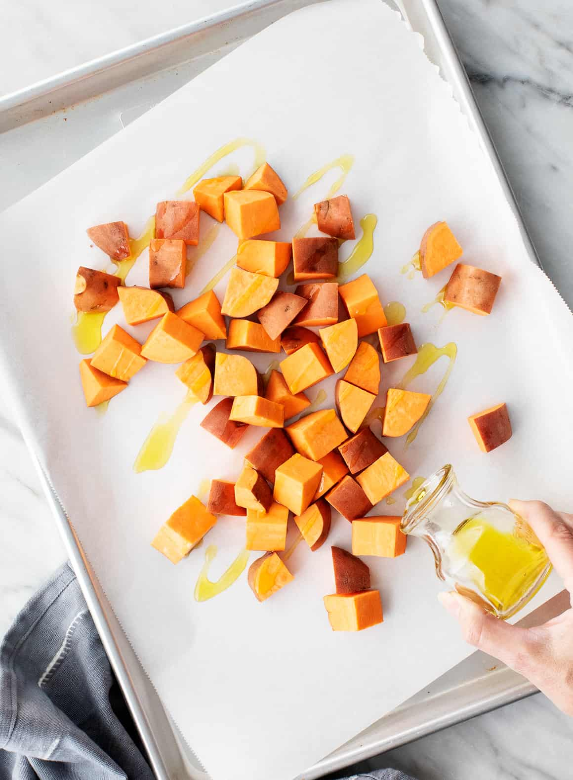 Sweet potato cubes on a baking sheet with olive oil