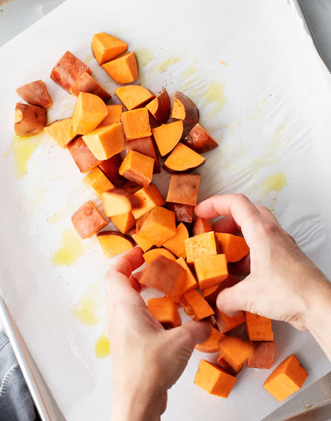 Hands tossing sweet potatoes with oil on a baking sheet