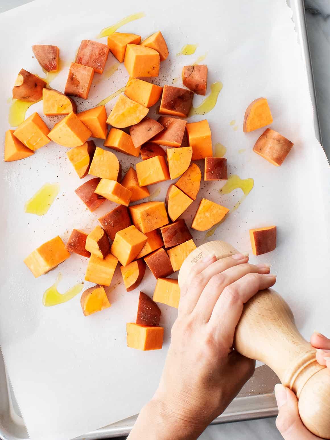 Hands seasoning sweet potato cubes with black pepper