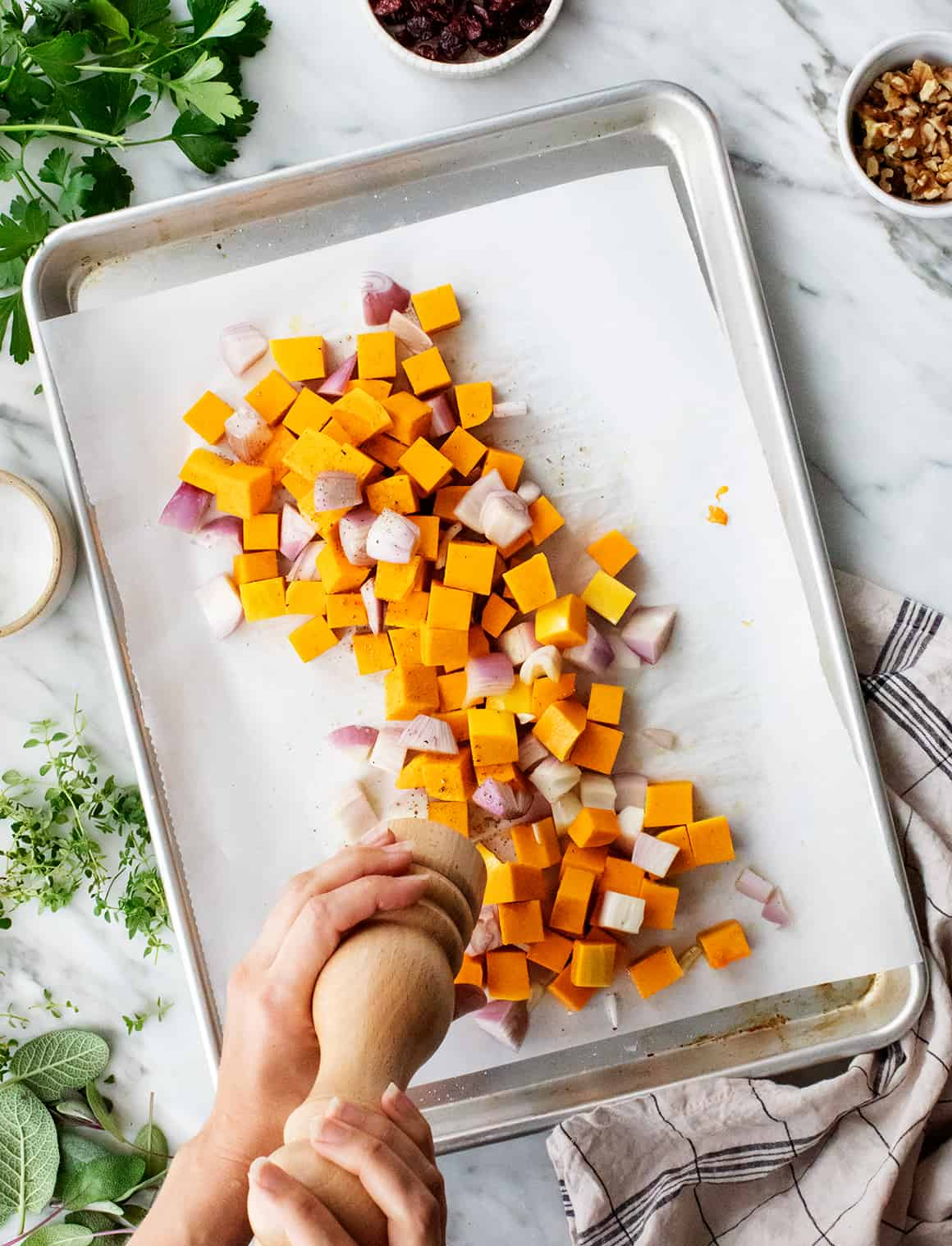 Diced butternut squash and shallots on a baking sheet