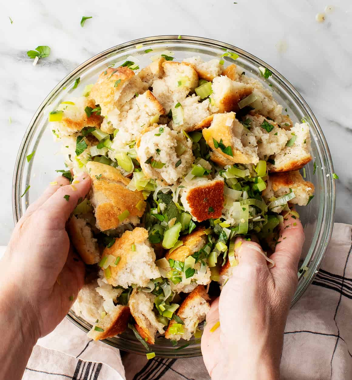 Hands mixing crusty bread with herbs, leeks, and celery