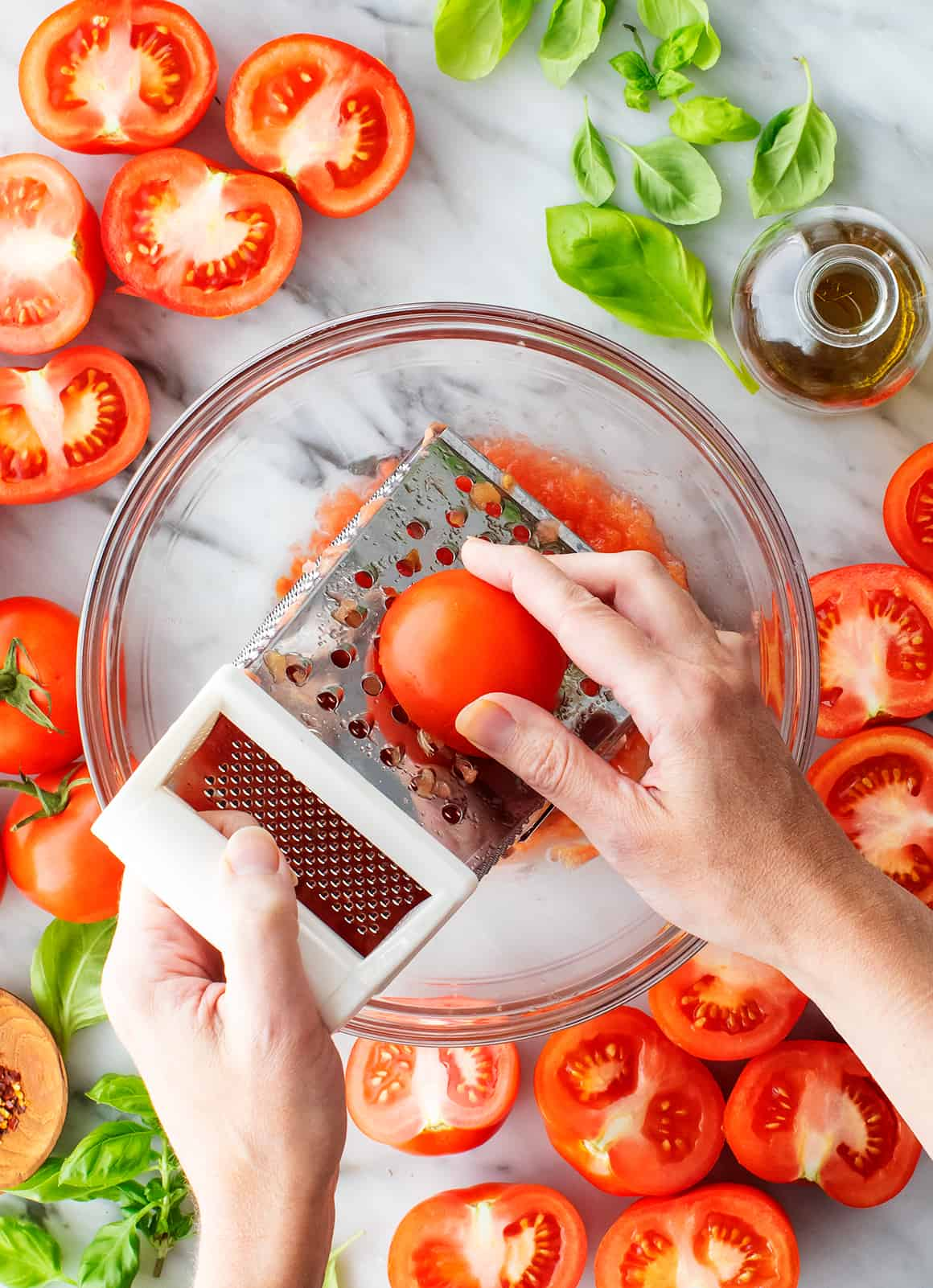 Hand grating halved tomato on a box grater over a large bowl